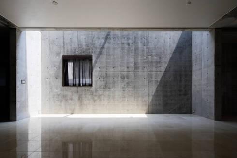 リビングの壁にトップライトからの光が差し込む: 鈴木賢建築設計事務所/SATOSHI SUZUKI ARCHITECT OFFICEが手掛けたリビングです。