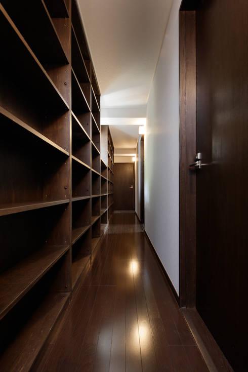造り付け書架の廊下兼書庫: 鈴木賢建築設計事務所/SATOSHI SUZUKI ARCHITECT OFFICEが手掛けた玄関&廊下&階段です。