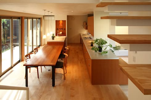 books and gardens 階段からキッチン方向: アーキシップス古前建築設計事務所が手掛けたキッチンです。