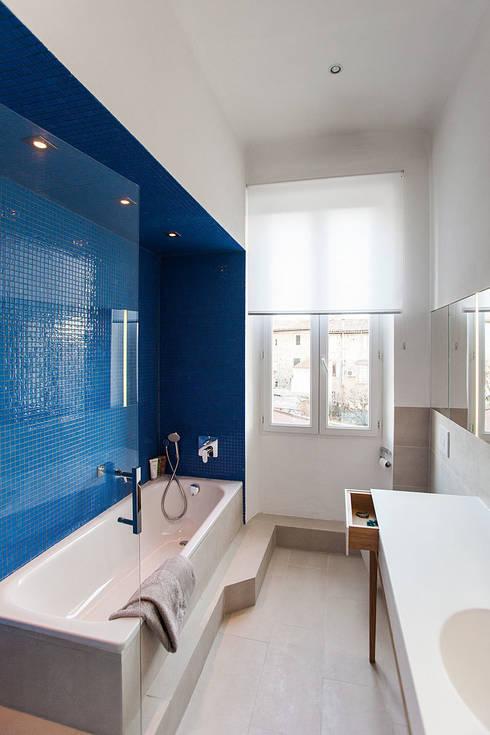 Une niche éclairée de mosaïque bleue apporte un caractère intimiste au moment du bain: Salle de bains de style  par Charlotte Raynaud Studio