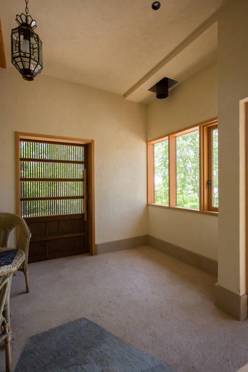 大泉の舎‐土間のある玄関: 有限会社中村建築事務所が手掛けた壁です。