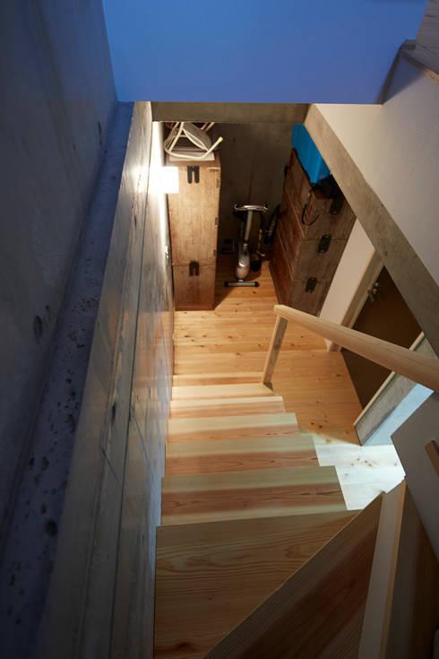 地下階段室: 一級建築士事務所co-designstudioが手掛けた廊下 & 玄関です。