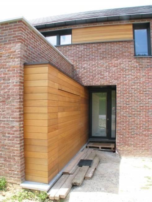 Le bardage qui dissimule une porte de garage guide vers la porte d'entrée principale.: Maisons de style  par dune Architecture sprl