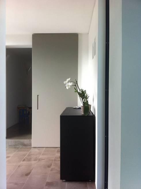 """The sliding door """"magic"""": Ingresso, Corridoio & Scale in stile  di SARA DALLA SERRA ARCHITETTO"""