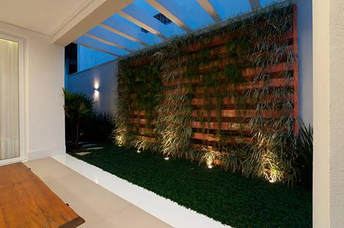 Casa de praia no litoral paulista prima pelo conforto e elegância: Jardins modernos por Guido Iluminação e Design