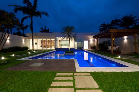 Casa de praia no litoral paulista prima pelo conforto e elegância: Piscinas modernas por Guido Iluminação e Design