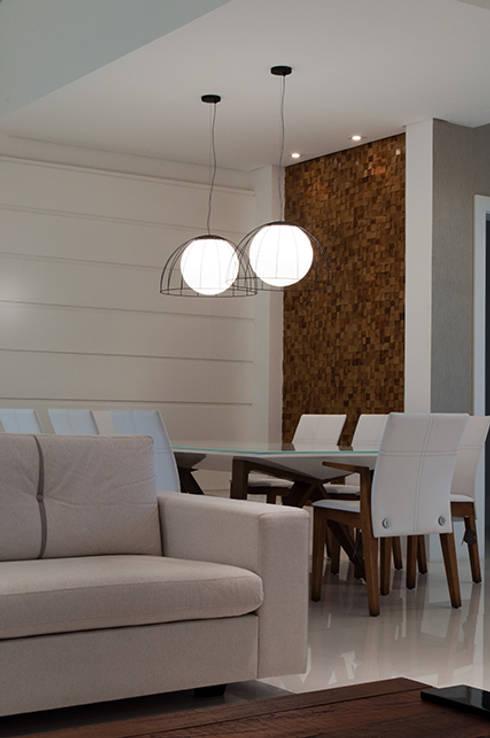 Casa de praia no litoral paulista prima pelo conforto e elegância: Salas de jantar modernas por Guido Iluminação e Design