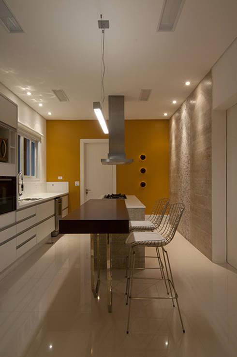 Casa de praia no litoral paulista prima pelo conforto e elegância: Cozinhas modernas por Guido Iluminação e Design