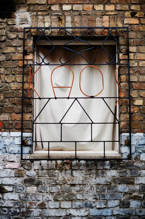 Fenstergitter aus Stahl mit Holzschriftzug:  Fenster & Tür von Volker Rueß