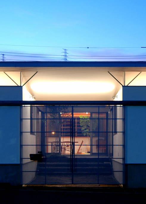 漆喰壁が映えるガレージ: 土居建築工房が手掛けた家です。