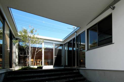 アプローチ上がると青い空: 土居建築工房が手掛けた庭です。