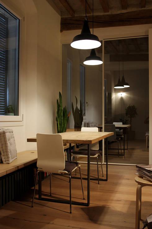 la zona pranzo con le porte scorrevoli riflettenti: Sala da pranzo in stile in stile Moderno di d'uopo