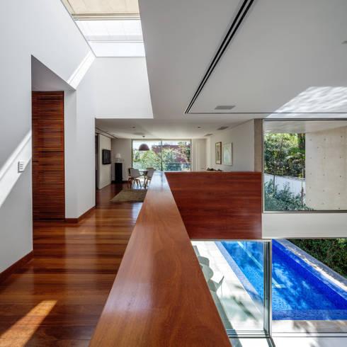 Residência MG: Corredores e halls de entrada  por Reinach Mendonça Arquitetos Associados