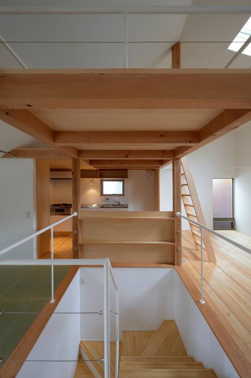 階段を通してキッチンを見る: (有)菰田建築設計事務所が手掛けた廊下 & 玄関です。