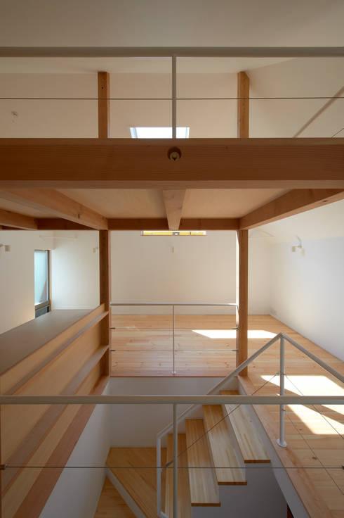 階段を通してリビングダイニングを見る: (有)菰田建築設計事務所が手掛けた廊下 & 玄関です。