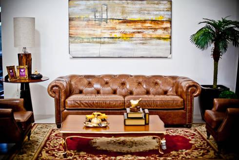 Sofá de couro legitimo.: Sala de estar  por VIA HAUS