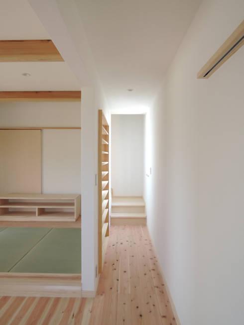 2階へ続く廊下の壁面のCDラック: 篠田 望デザイン一級建築士事務所が手掛けた玄関&廊下&階段です。