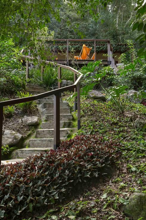 Casa de praia - Guaecá SP: Jardins rústicos por Lucia Manzano