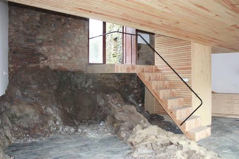 Vista da escada com o afloramento rochoso: Salas de estar modernas por Atelier do Corvo