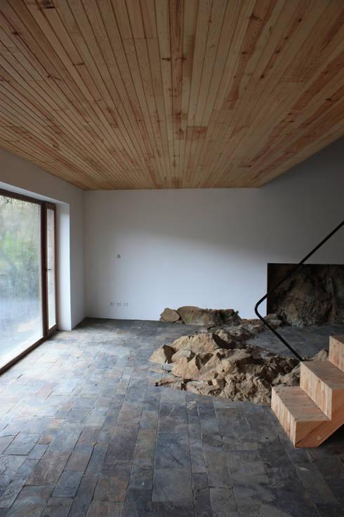 Vista da sala com o afloramento rochoso: Salas de estar modernas por Atelier do Corvo
