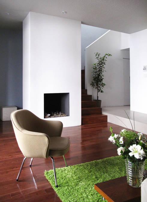 coin salon devant une fausse cheminée de bougies et escalier pour 1er étage : Salon de style  par Studio Pan
