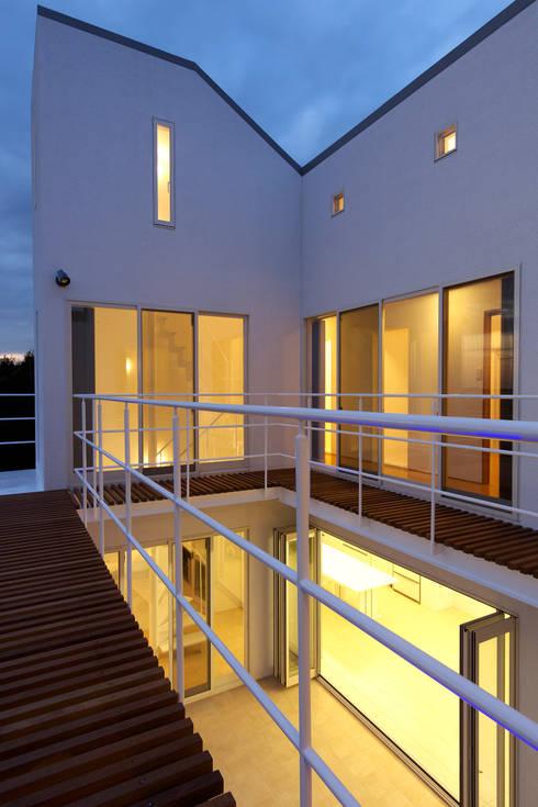 2階デッキからコート: (有)設計工房TOGAWAが手掛けたテラス・ベランダです。