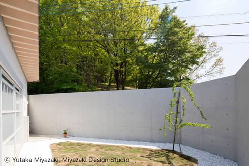 渡り廊下と屋根上デッキの家・奥庭: 宮崎豊・MDS建築研究所が手掛けた庭です。