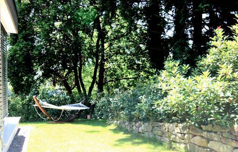 Garten mit Steinmauer und eingewachsenem Baumumfeld: ausgefallener Garten von raumatmosphäre pantanella