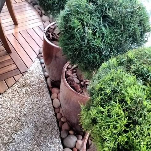 Vasos, pedras, pedriscos e deck: Varanda, alpendre e terraço  por Amaria Gonçalves - Design Paisagismo