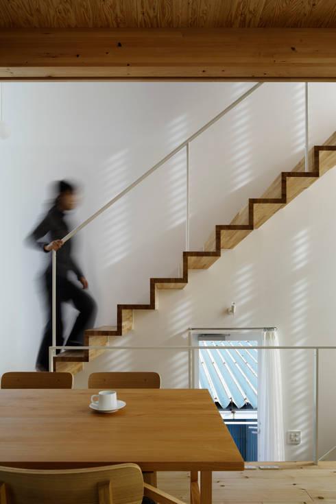 シナの木と白い家: 高橋真紀建築設計事務所が手掛けた廊下 & 玄関です。