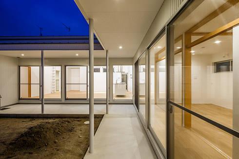 コの字の家 中庭夕景: 腰越耕太建築設計事務所が手掛けた庭です。