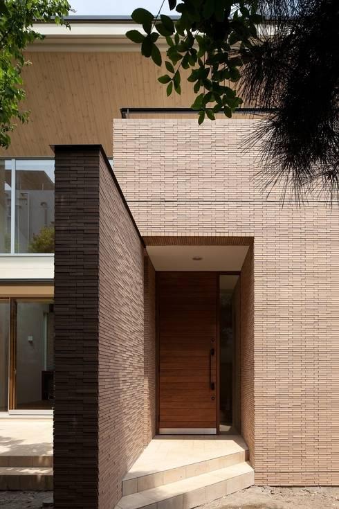 壁に誘われてアプローチする玄関: シーズ・アーキスタディオ建築設計室が手掛けた家です。