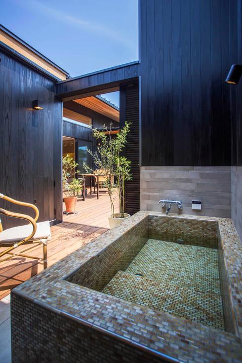 外風呂のある暮らし: イシマルデザイン 一級建築士事務所が手掛けた浴室です。