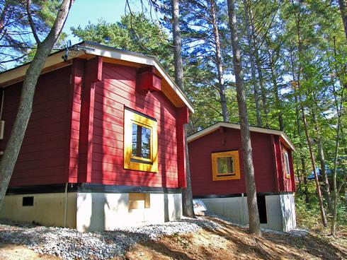 森の斜面側には大きな窓: Cottage Style / コテージスタイルが手掛けたガレージ/物置です。