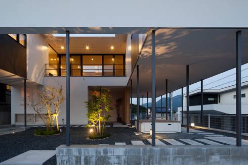 軒下に照らし出される樹々の影: 松本匡弘建築設計事務所が手掛けた家です。