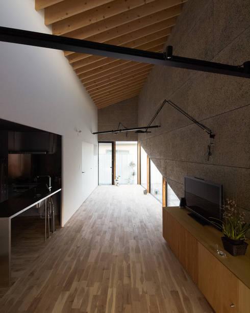 白いコアボリュームとそれを囲むリビングダイニングと客間: atelier CHOCOLATEが手掛けたダイニングです。