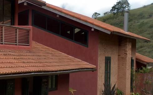 Fachada  com paredes em tijolo aparente pintura a base de cal: Casas rústicas por Ronald Ingber Arquitetura