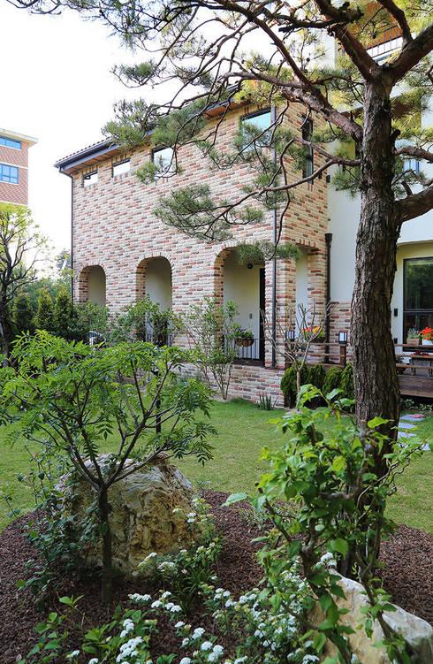 정원에서 바라본 남측 파사드: OUA 오유에이의  주택