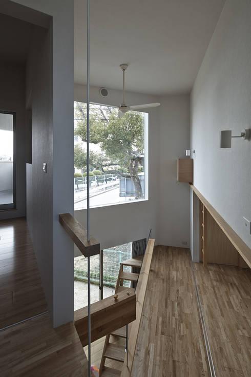 2階の階段からクスの木の方向を見る、左が寝室、右が子供スペース: 宮武淳夫建築+アルファ設計が手掛けた廊下 & 玄関です。