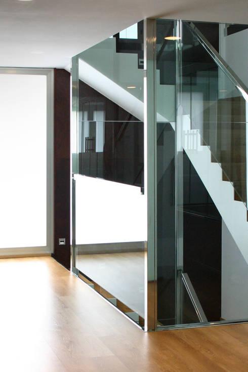 Escalera con dos cristaleras enfrentadas a modo de barandillas. La Pobla. Chiralt Arquitectos. : Vestíbulos, pasillos y escaleras de estilo  de Chiralt Arquitectos