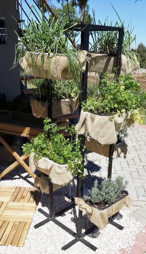 Horta vertical em estrutura metálica: Jardins tropicais por Ésse Arquitetura e Interiores