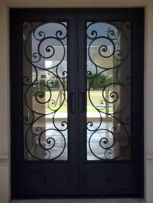 Puerta de entrada: Ventanas y puertas de estilo  por Del Hierro Design