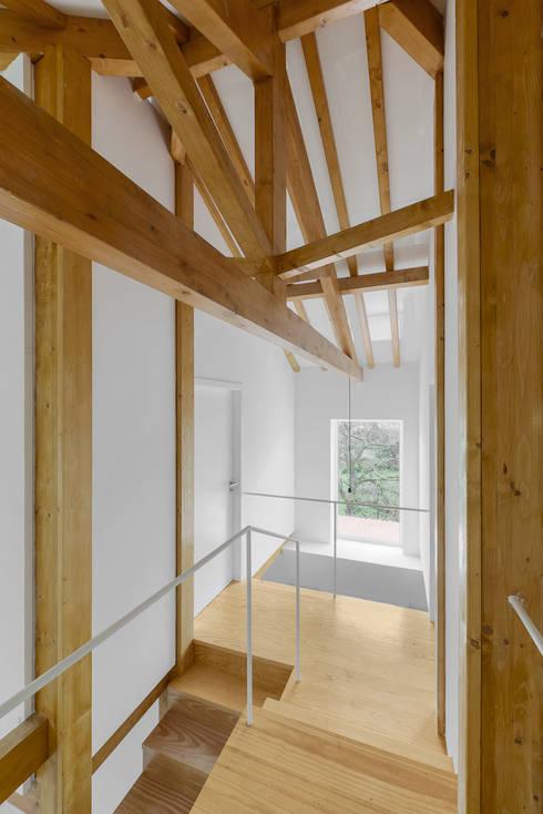 Estrutura em asna do telhado: Corredores e halls de entrada  por Corpo Atelier