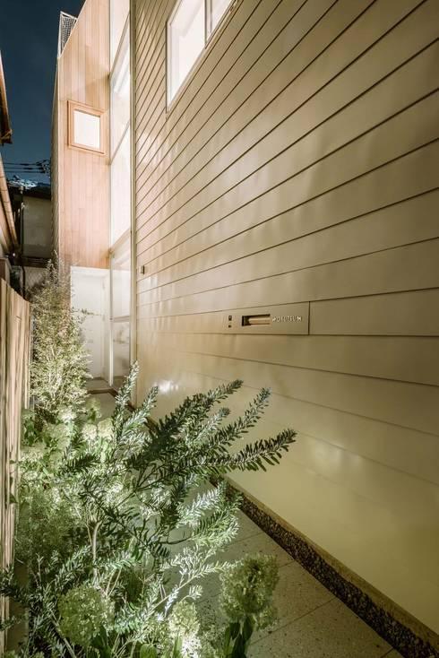 アプローチ夕景: ディンプル建築設計事務所が手掛けた家です。