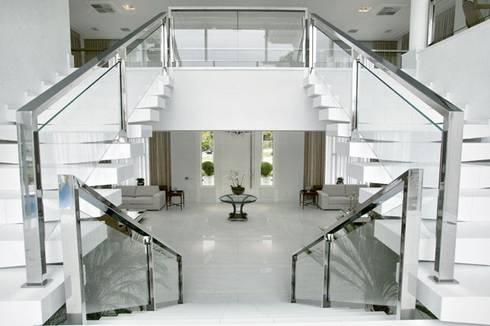 Branco como protagonista nesta casa no litoral brasileiro .: Corredores e halls de entrada  por Bianka Mugnatto Design de Interiores