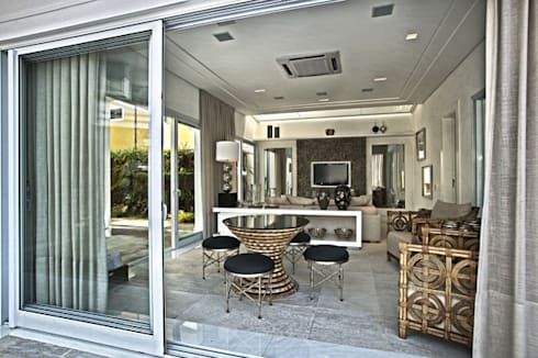 Branco como protagonista nesta casa no litoral brasileiro .: Salas multimídia ecléticas por Bianka Mugnatto Design de Interiores