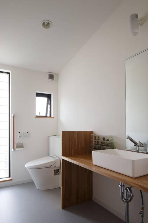 庭と繋がるテラスハウス: アトリエグローカル一級建築士事務所が手掛けた浴室です。