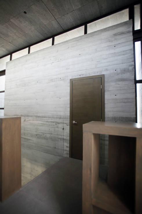Cubo de concreto con acceso hacia home theater / puente doble altura: Pasillos y recibidores de estilo  por WRKSHP arquitectura/urbanismo