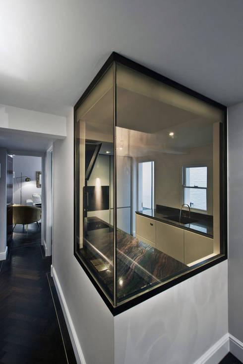 Hallway and kitchen window:  Corridor & hallway by ÜberRaum Architects