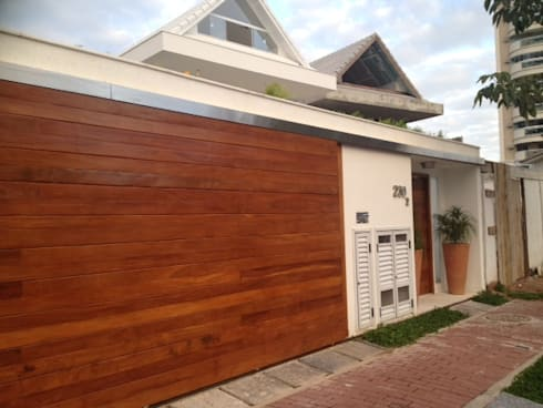 Portão da garagem deslizante em madeira.: Garagens e edículas tropicais por Studio HG Arquitetura